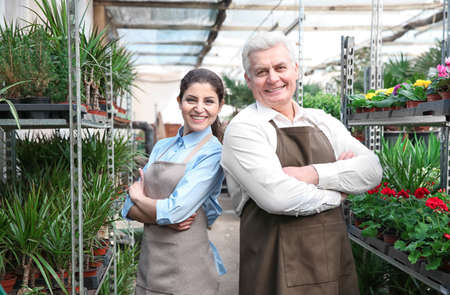 Photo pour Male and female florists in greenhouse - image libre de droit