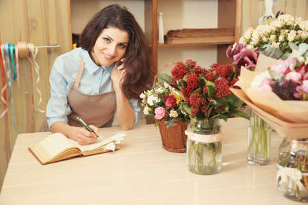 Photo pour Beautiful woman florist using mobile phone while writing on notebook in flower shop - image libre de droit