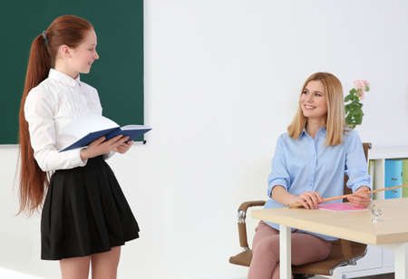 Photo for Schoolgirl answering at blackboard in classroom - Royalty Free Image