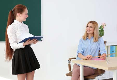 Foto de Schoolgirl answering at blackboard in classroom - Imagen libre de derechos