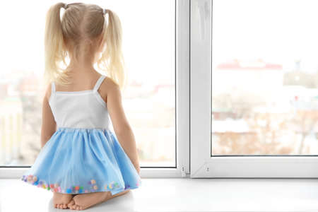 Photo pour Cute little girl sitting on windowsill - image libre de droit