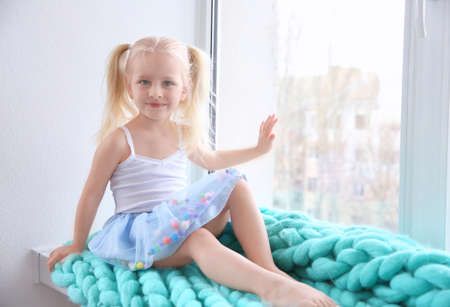 Photo for Cute little girl sitting on windowsill - Royalty Free Image