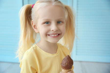 Foto de Cute little girl eating ice cream on folding screen background - Imagen libre de derechos