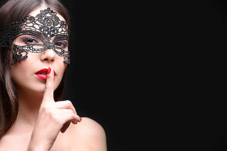 Photo for Beautiful young woman in mask on black background - Royalty Free Image