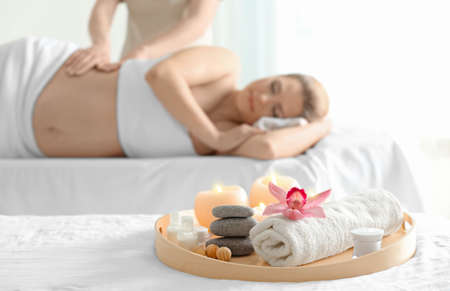 Photo pour Beautiful spa composition and blurred pregnant woman on background - image libre de droit