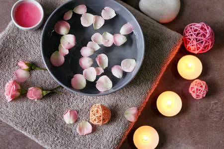 Foto de Beautiful spa composition of flower petals with water in bowl and candles on gray background - Imagen libre de derechos
