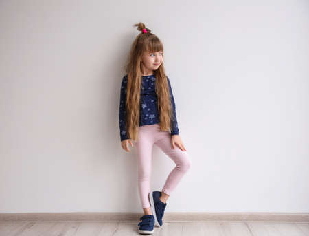 Photo pour Little fashion girl posing in light room - image libre de droit