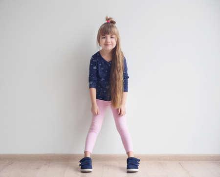 Photo pour Little fashion girl posing in light room - image libre de droit