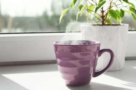 Foto de Cup of delicious hot drink on window sill - Imagen libre de derechos