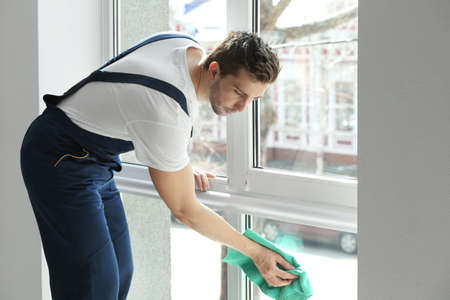 Foto de Young man cleaning window in office - Imagen libre de derechos
