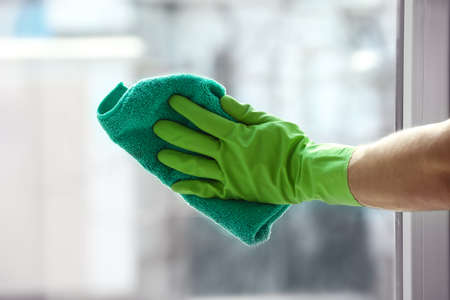 Foto de Hand of young man cleaning window in office - Imagen libre de derechos