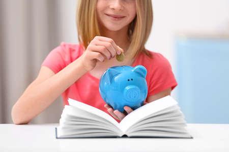 Foto de Cute girl putting coin into piggy bank at home, closeup - Imagen libre de derechos