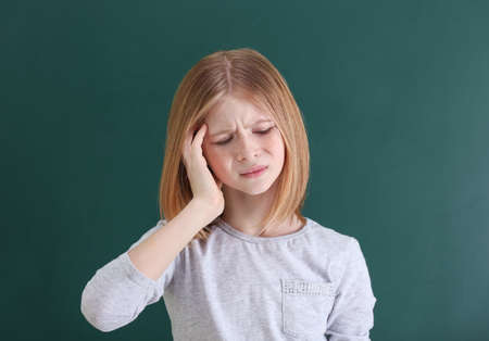 Photo for Cute girl suffering from headache on color background - Royalty Free Image