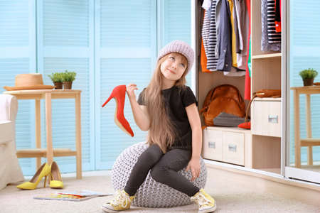 Photo pour Cute little girl with fashionable shoes at home - image libre de droit