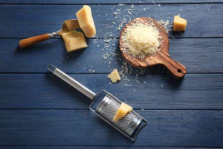 Foto de Wooden board with cheese and grater on table - Imagen libre de derechos