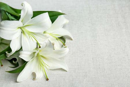 Foto de Beautiful lilies on fabric background - Imagen libre de derechos