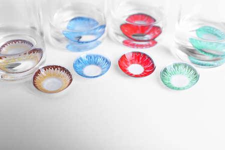 Foto de Color contact lenses and glass bottles on white background - Imagen libre de derechos