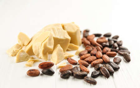 Foto de Composition with cocoa butter and beans on wooden background - Imagen libre de derechos