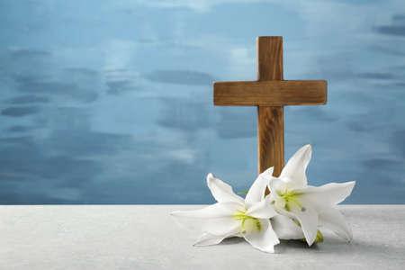 Photo pour Wooden cross and white lily on table - image libre de droit