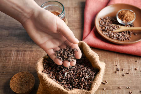 Photo for Human hand taking pile of cocoa nibs from bag - Royalty Free Image