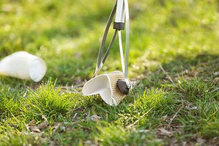 Foto de Volunteer picking up litter from grass, closeup - Imagen libre de derechos