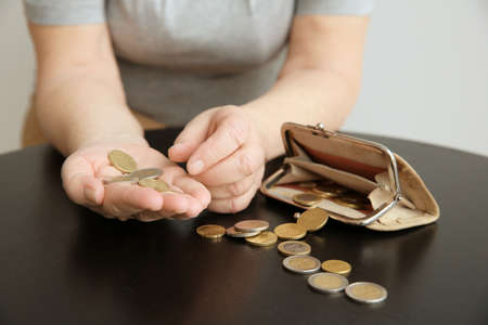 Photo for Senior woman counting coins while sitting at table, closeup. Poverty concept - Royalty Free Image