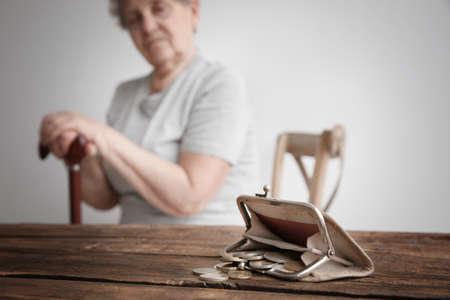 Foto de Purse with coins and blurred senior woman on background. Poverty concept - Imagen libre de derechos