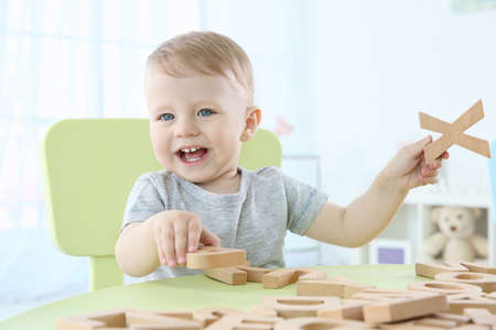 Foto de Cute little child playing with letters at home - Imagen libre de derechos