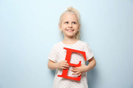Foto de Cute little girl with letter E on light background - Imagen libre de derechos