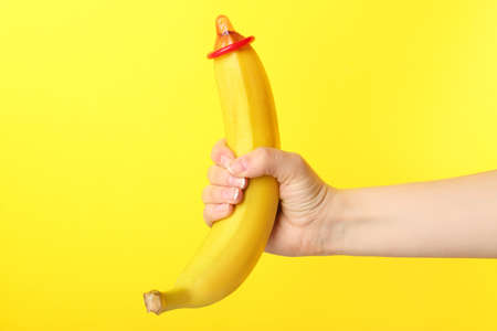 Foto de Woman holding banana with condom against color background. Safe sex concept - Imagen libre de derechos