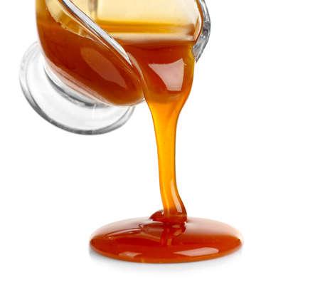 Foto de Pouring caramel sauce onto white background - Imagen libre de derechos
