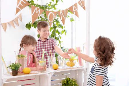 Foto de Cute little kids selling lemonade at counter - Imagen libre de derechos