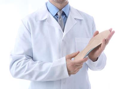 Foto de Male orthopedist with insole on white background, closeup - Imagen libre de derechos