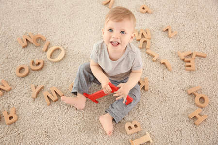 Foto de Cute little child with wooden letters sitting on carpet at home - Imagen libre de derechos