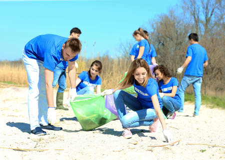 Photo pour Young volunteers gathering garbage outdoors - image libre de droit