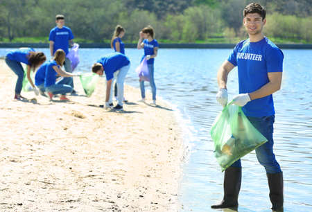 Photo for Handsome young volunteer with team gathering garbage on river bank - Royalty Free Image