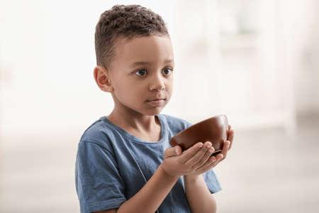 Foto de Cute little boy with bowl on blurred background. Poverty concept - Imagen libre de derechos