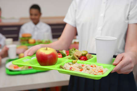 Foto de Girl holding tray with delicious food in school canteen, closeup - Imagen libre de derechos