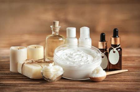 Foto de Composition of Shea butter with cosmetic products on wooden table - Imagen libre de derechos
