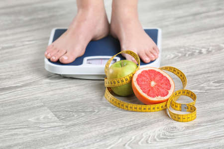Photo for Woman standing on scales near fruits and measuring tape on wooden floor. Concept of weight loss - Royalty Free Image