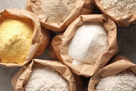 Foto de Paper bags with different types of flour on gray background, closeup - Imagen libre de derechos