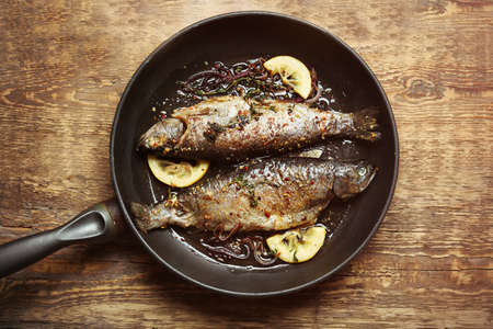 Photo for Frying pan with tasty trout fish on wooden background - Royalty Free Image