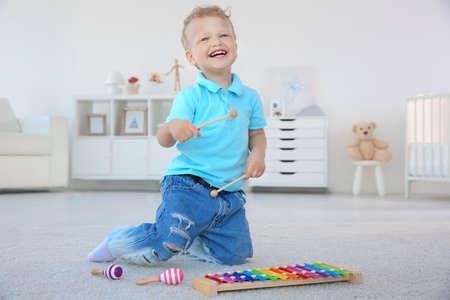 Photo pour Cute little boy with xylophone at home - image libre de droit
