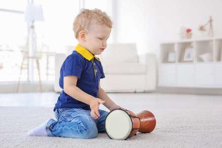 Photo pour Cute little boy with drum on floor at home - image libre de droit
