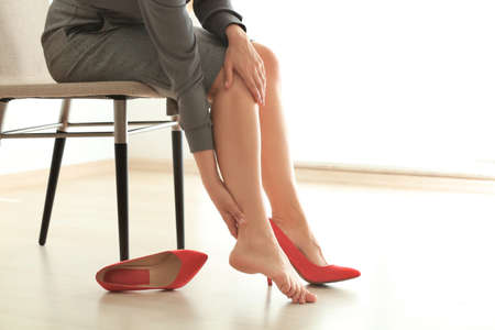 Photo pour Young woman suffering from leg pain in office because of uncomfortable shoes - image libre de droit