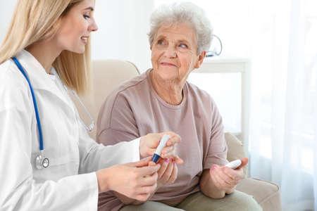 Foto de Young nurse examining elderly woman with glucometer at home - Imagen libre de derechos