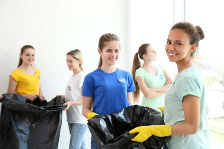 Photo for Young volunteers with garbage bags indoors - Royalty Free Image