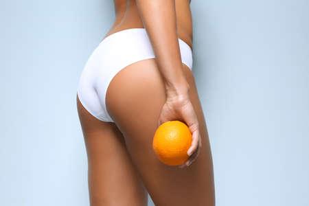 Photo pour Young woman holding orange on light background. Cellulite problem concept - image libre de droit