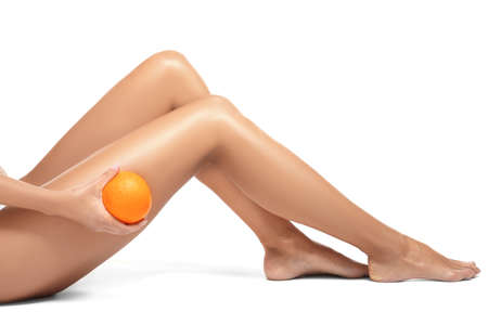 Photo for Female legs and orange on white background. Cellulite problem concept - Royalty Free Image