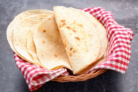 Foto de Wicker basket with delicious tortillas on table - Imagen libre de derechos